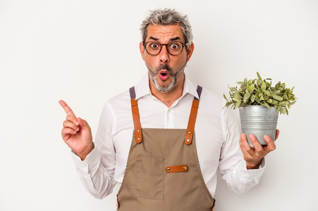 Middle age gardener caucasian man holding a plant isolated on white background  pointing to the side