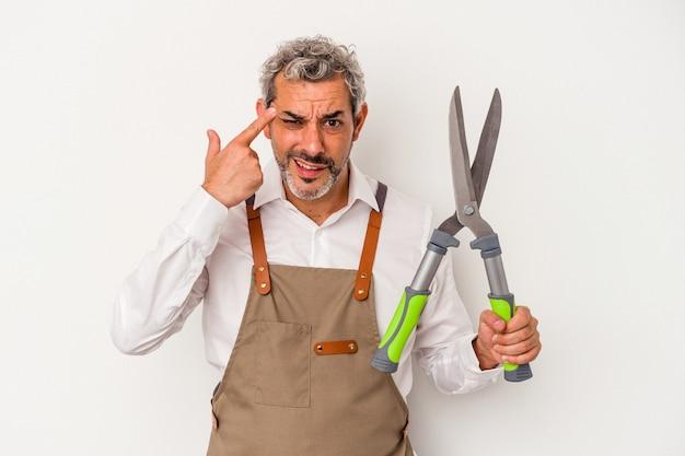 집게 손가락으로 실망 제스처를 보여주는 흰색 배경에 고립 가위를 들고 중년 정원사 남자.