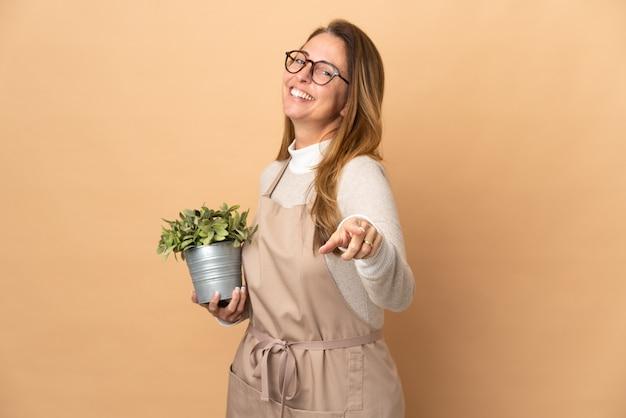 幸せな表情で正面を指すベージュの背景に分離された植物を保持している中年の庭師の女性