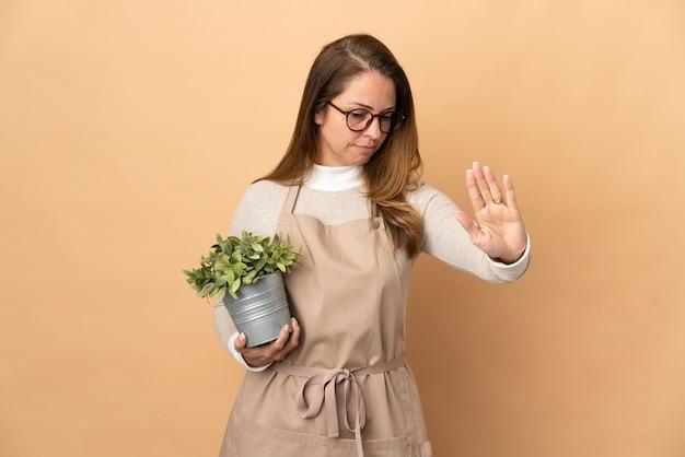 베이지 색 중지 제스처를 만들고 실망에 고립 된 식물을 들고 중년 정원사 여자