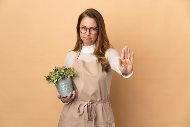 중지 제스처를 만드는 베이지 색 벽에 고립 된 식물을 들고 중년 정원사 여자
