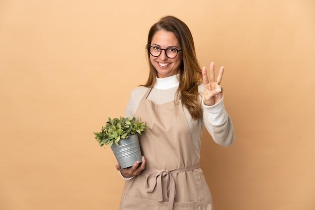 孤立した植物を保持している中年の庭師の女性