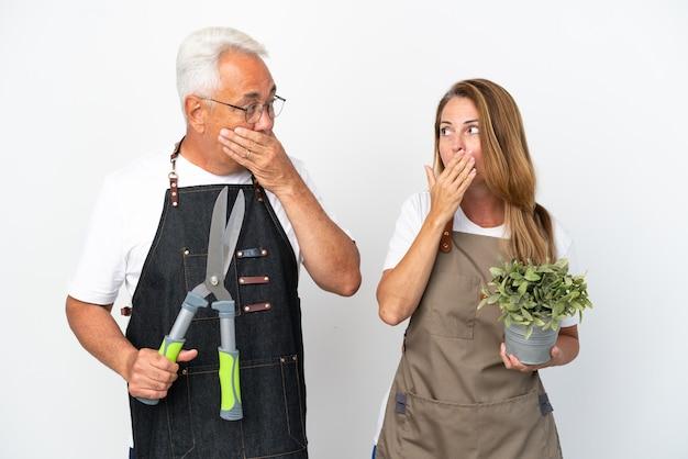 不適切なことを言うために手で口を覆っている白い背景に分離された植物とはさみを持っている中年の庭師