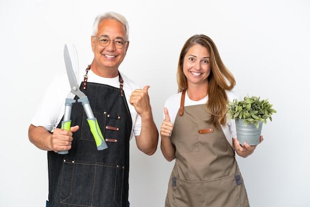 Садовники среднего возраста держат растение и ножницы, изолированные на белом фоне, показывая большой палец вверх обеими руками и улыбаясь