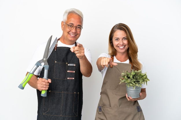 Садовники среднего возраста держат растение и ножницы на белом фоне с уверенным выражением лица указывают пальцем на вас