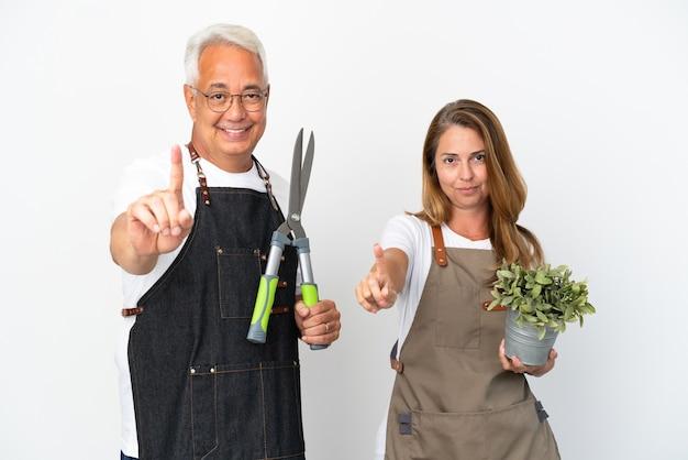 Садовники среднего возраста держат растение и ножницы на белом фоне, показывая и поднимая палец