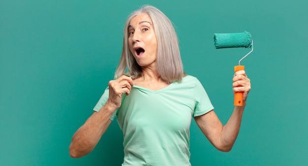 彼女の壁を飾るペイントローラーを持つ中年の白髪の女性