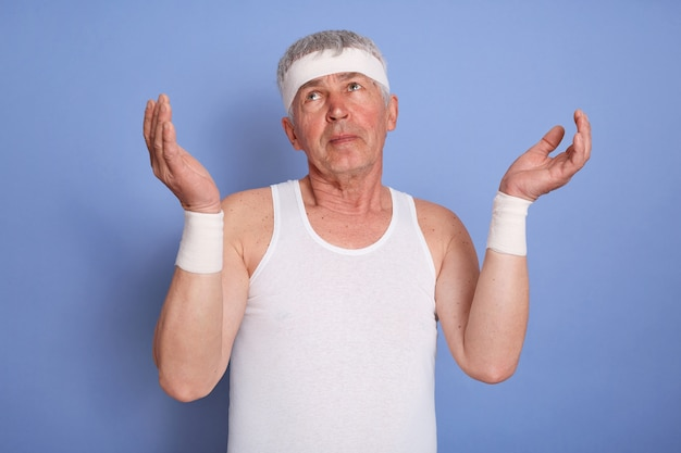 Middle age handsome sportsman, looks clueless and confused, keep arms raised, has no idea, wearing white sleeveless t-shirt and hear band, standing isolated.