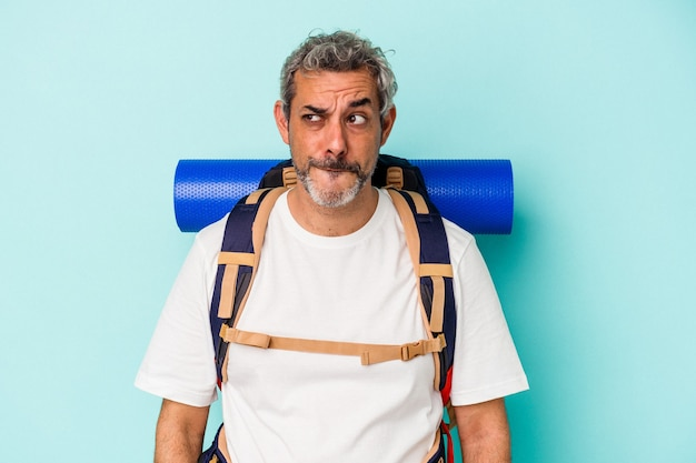 Middle age hiker caucasian man isolated on blue background  confused, feels doubtful and unsure.
