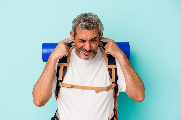 Middle age hiker caucasian man isolated on blue background  covering ears with hands.