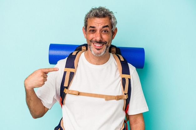 Middle age hiker caucasian man isolated on blue background  person pointing by hand to a shirt copy space, proud and confident