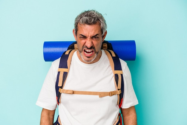 Middle age hiker caucasian man isolated on blue background  screaming very angry and aggressive.