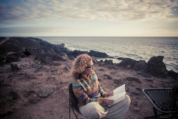 Дама среднего возраста со светлыми вьющимися волосами и бумажной книгой сидит на открытом воздухе на берегу океана, наслаждаясь свободой и альтернативным отдыхом или досугом в контакте с природой