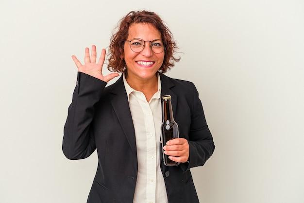 白い背景で隔離のビールを保持している中年ラテンビジネスの女性は、指で5番を示して陽気に笑っています。