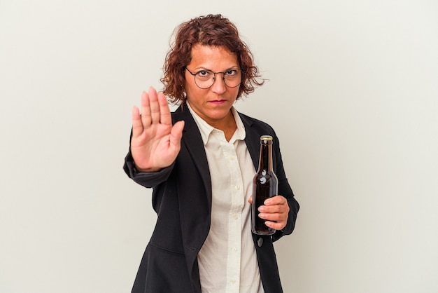 一時停止の標識を示す伸ばした手で立っている白い背景で隔離のビールを保持している中年ラテンビジネス女性は、あなたを防ぎます。