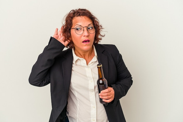 ゴシップを聴こうとしている白い背景で隔離のビールを保持している中年ラテンビジネス女性。