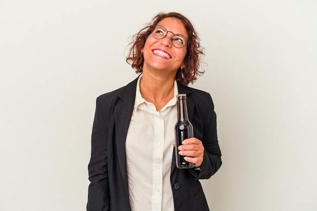 Middle age latin business woman holding a beer isolated on white background dreaming of achieving goals and purposes