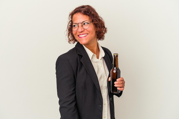 Middle age latin business woman holding a beer isolated on white background looks aside smiling, cheerful and pleasant.