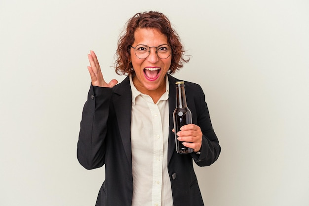 Middle age latin business woman holding a beer isolated on white background receiving a pleasant surprise, excited and raising hands.