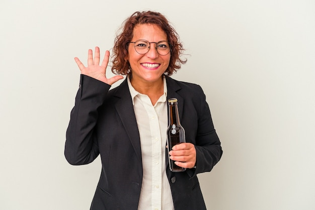 Middle age latin business woman holding a beer isolated on white background smiling cheerful showing number five with fingers.