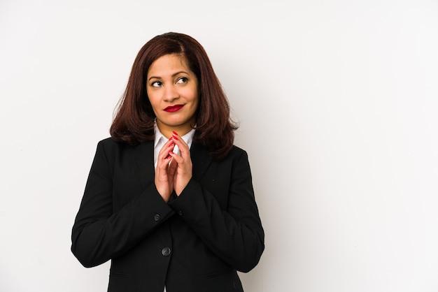 Латинская бизнес-леди среднего возраста изолирована, составляя план в уме, создавая идею.