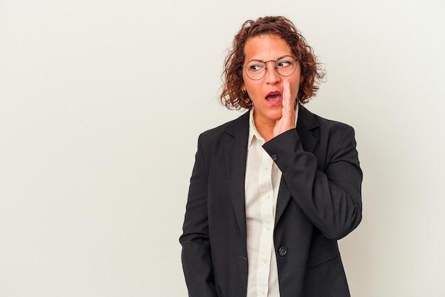 白い背景で隔離の中年ラテンビジネス女性は秘密のホットブレーキニュースを言って脇を見ています