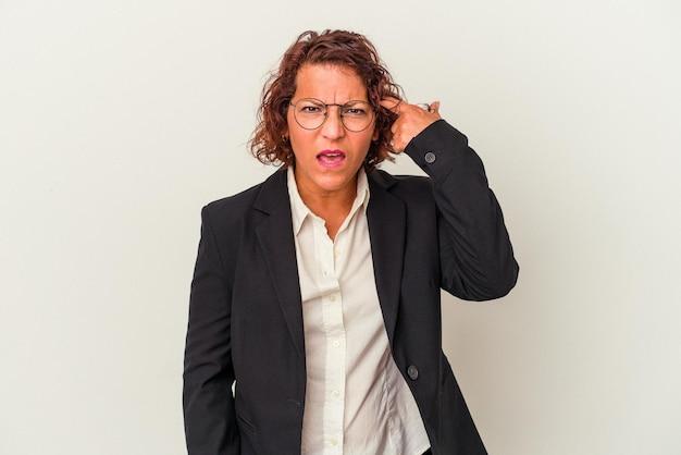 人差し指で失望のジェスチャーを示す白い背景で隔離の中年ラテンビジネス女性。