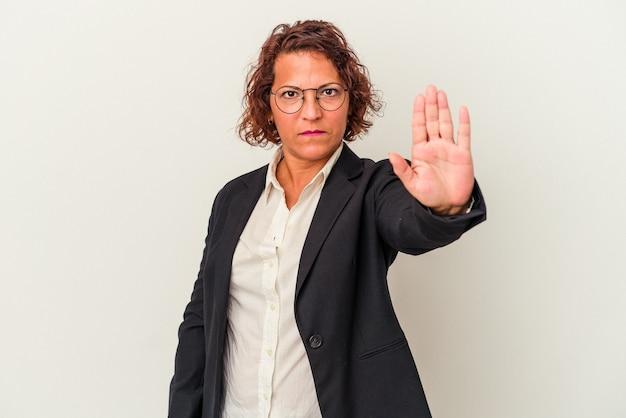 一時停止の標識を示す伸ばした手で立っている白い背景に分離された中年ラテンビジネス女性は、あなたを防ぎます。