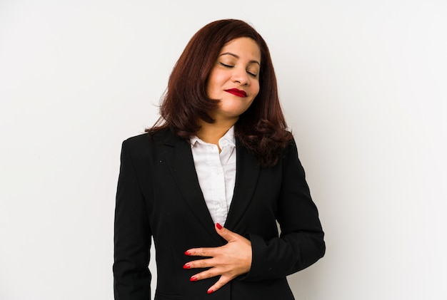 Middle age latin business woman isolated touches tummy, smiles gently, eating and satisfaction concept.