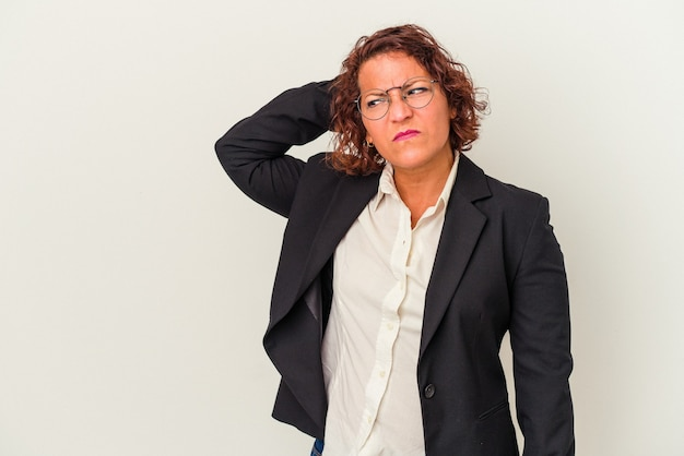 Middle age latin business woman isolated on white background touching back of head, thinking and making a choice.