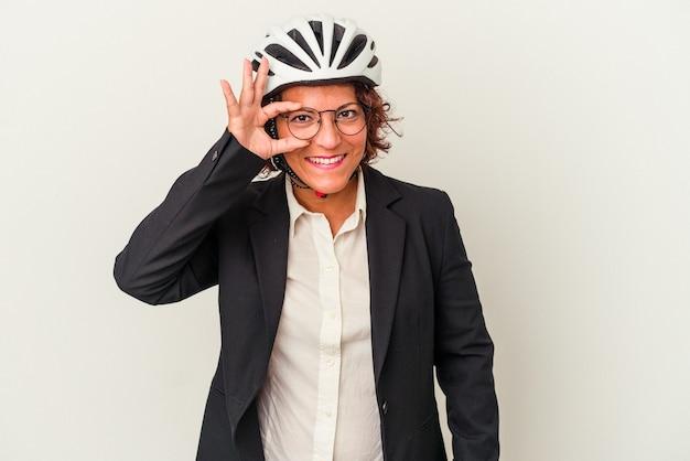 白い背景で隔離の自転車のヘルメットを身に着けている中年ラテンビジネスの女性は、目に大丈夫なジェスチャーを維持することに興奮しました。