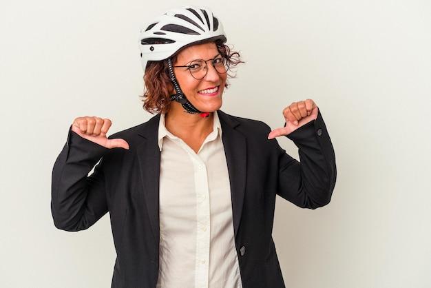 白い背景で隔離の自転車のヘルメットを身に着けている中年のラテンビジネスの女性は、誇りと自信を持って、従うべき例を感じます。