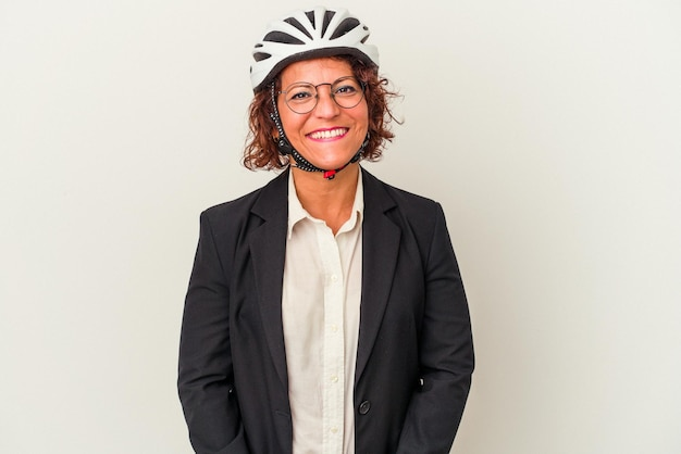 幸せ、笑顔、陽気な白い背景で隔離の自転車のヘルメットを身に着けている中年ラテンビジネス女性。