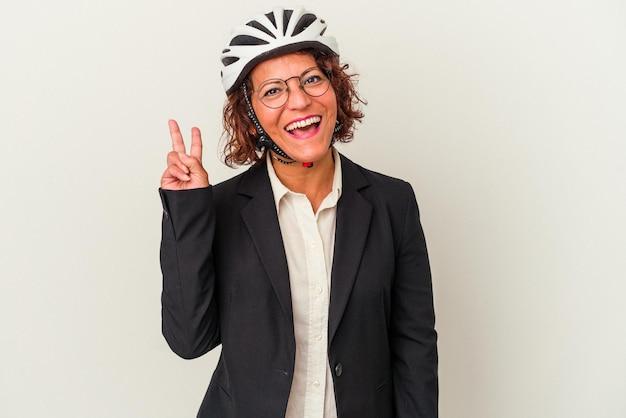 白い背景で隔離の自転車のヘルメットを身に着けている中年ラテンビジネスの女性は、指で平和のシンボルを示して楽しくてのんき。