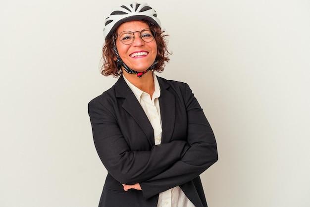 笑って楽しんでいる白い背景で隔離の自転車のヘルメットを身に着けている中年ラテンビジネス女性。