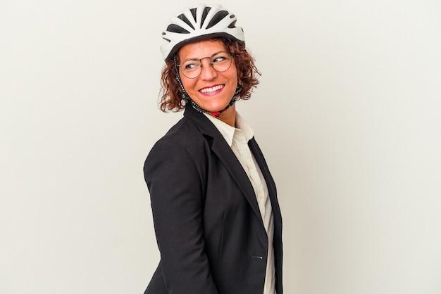 白い背景で隔離の自転車のヘルメットを身に着けている中年ラテンビジネスの女性は、笑顔、陽気で楽しい脇に見えます。