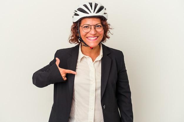 シャツのコピースペースを手で指している白い背景の人に分離された自転車のヘルメットを身に着けている中年ラテンビジネス女性、誇りと自信を持って
