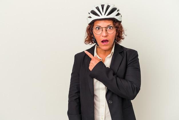側面を指している白い背景で隔離の自転車のヘルメットを身に着けている中年ラテンビジネス女性