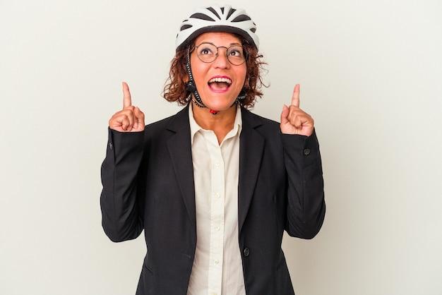 口を開けて逆さまを指している白い背景で隔離の自転車のヘルメットを身に着けている中年ラテンビジネス女性。 Premium写真