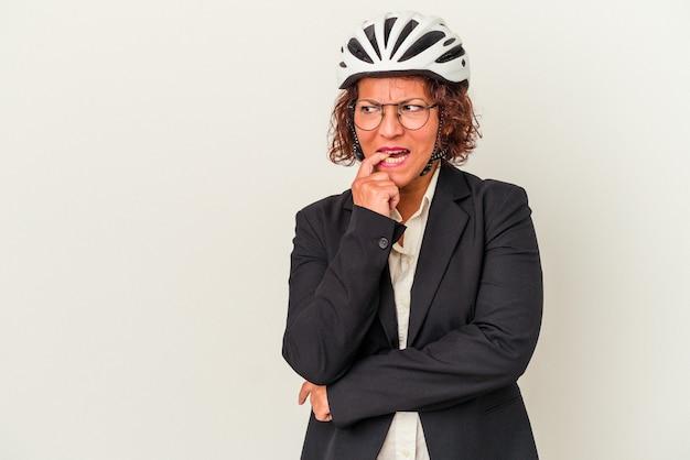 白い背景で隔離の自転車のヘルメットを身に着けている中年ラテンビジネスの女性は、コピースペースを見ている何かについて考えてリラックスしました。