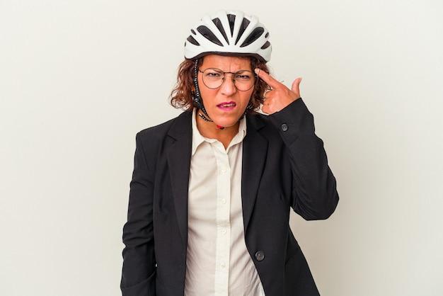 人差し指で失望のジェスチャーを示す白い背景で隔離の自転車のヘルメットを身に着けている中年ラテンビジネス女性。