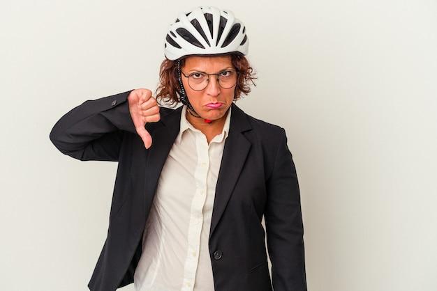 嫌いなジェスチャーを示す白い背景で隔離の自転車のヘルメットを身に着けている中年のラテンビジネスの女性は、親指を下に向けます。不一致の概念。