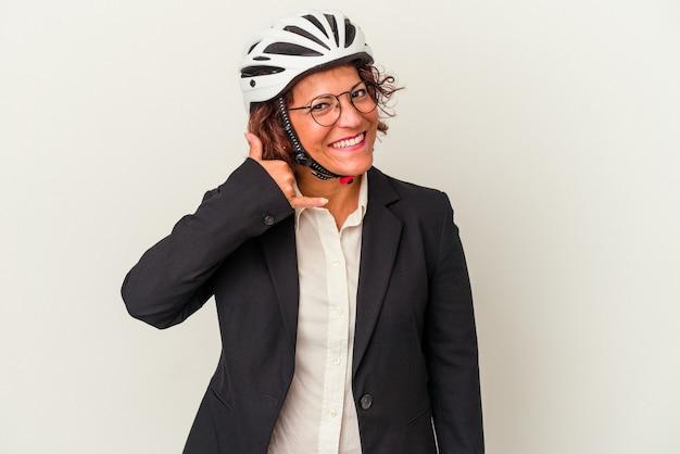 指で携帯電話の呼び出しジェスチャーを示す白い背景で隔離の自転車のヘルメットを身に着けている中年ラテンビジネス女性。
