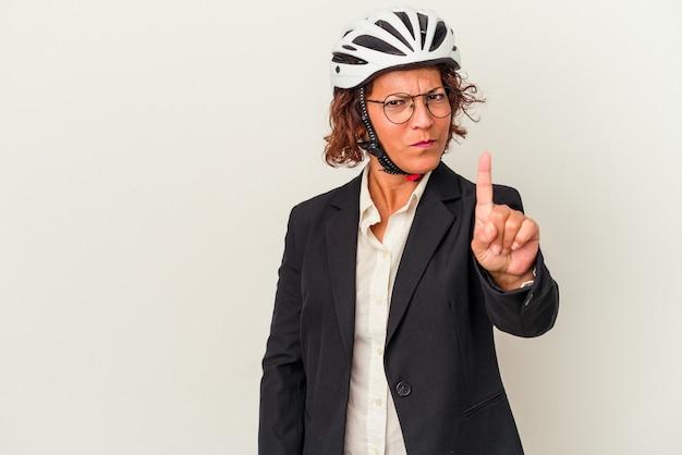 指でナンバーワンを示す白い背景で隔離の自転車のヘルメットを身に着けている中年ラテンビジネス女性。