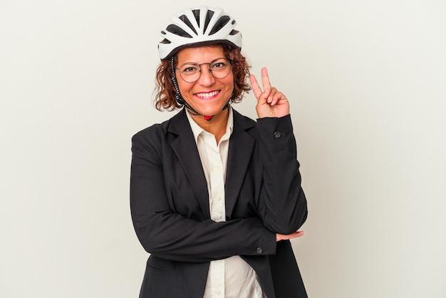 指で2番目を示す白い背景で隔離の自転車のヘルメットを身に着けている中年ラテンビジネス女性。