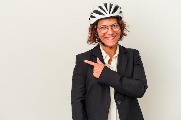 空白のスペースで何かを見せて、笑顔で脇を指して、白い背景で隔離の自転車のヘルメットを身に着けている中年ラテンビジネスの女性。