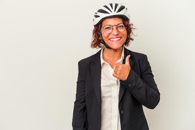 笑顔と親指を上げる白い背景で隔離の自転車のヘルメットを身に着けている中年ラテンビジネス女性