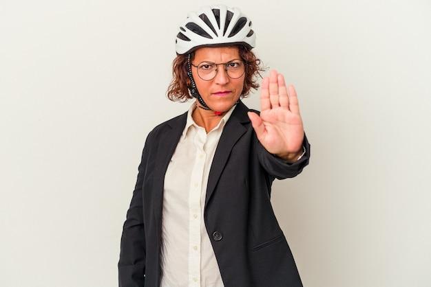 一時停止の標識を示す伸ばした手で立っている白い背景で隔離の自転車のヘルメットを身に着けている中年のラテンビジネスの女性は、あなたを防ぎます。