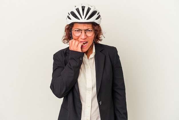 Middle age latin business woman wearing a bike helmet isolated on white background biting fingernails, nervous and very anxious.