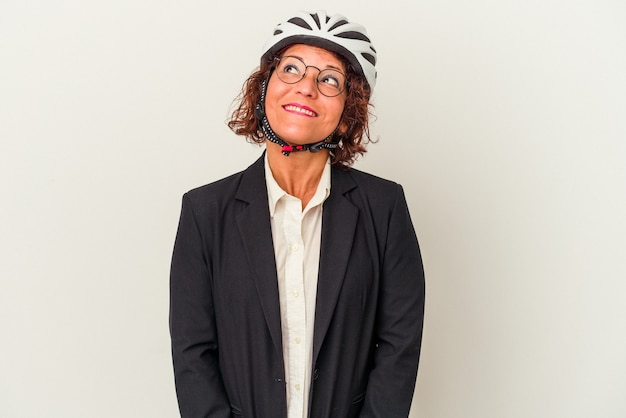 Middle age latin business woman wearing a bike helmet isolated on white background dreaming of achieving goals and purposes